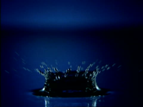high speed bcu water drop splashing into dark blue water, side view - splashing droplet stock videos and b-roll footage