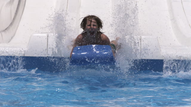high speed boy coming down water chute, to camera, spain. (individual frames may also be used as a still image. each frame in its raw state is about 6mb or about 12mb as a 16 bit tiff) - water slide stock videos & royalty-free footage