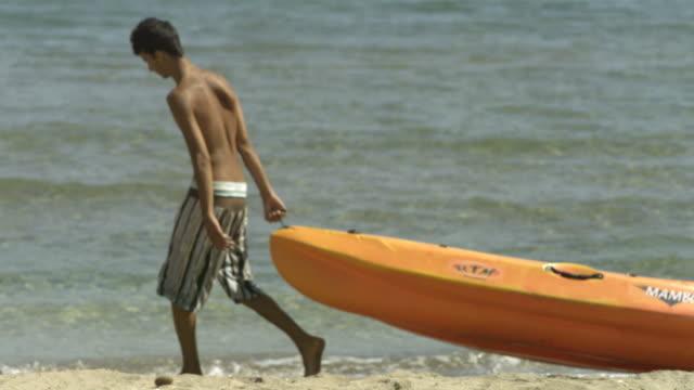 High Speed Boy dragging kayak on beach, Spain.