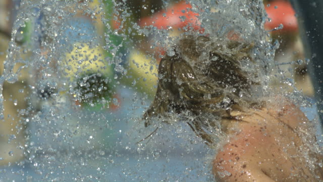 high speed boy runs through water shower, spain, close up. (individual frames may also be used as a still image. each frame in its raw state is about 6mb or about 12mb as a 16 bit tiff) - long hair stock videos & royalty-free footage