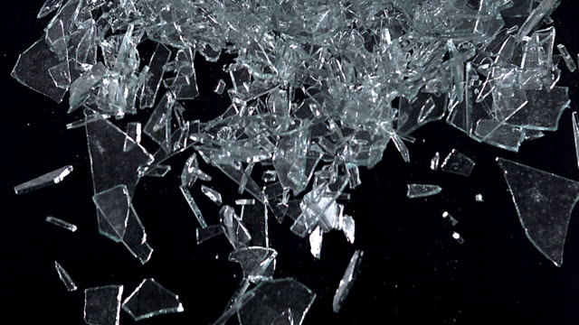 high speed broken glass falling against black background, 1000 fps - campo gravitazionale video stock e b–roll
