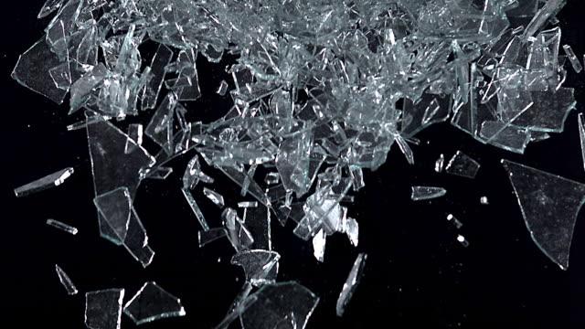 high speed broken glass falling against black background, 1000 fps - gravitationsfält bildbanksvideor och videomaterial från bakom kulisserna