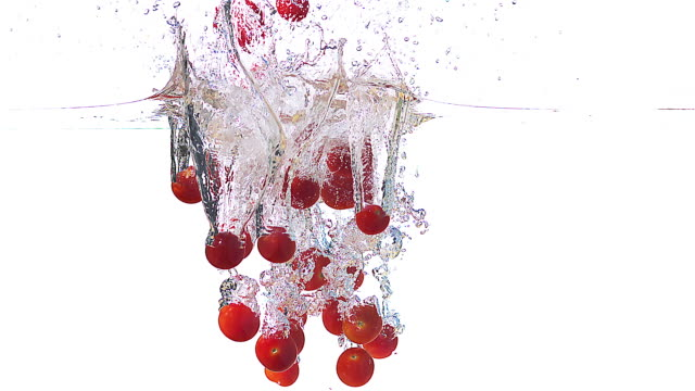 high speed cherry tomatoes falling in to water 1000fps - alta sensibilità video stock e b–roll