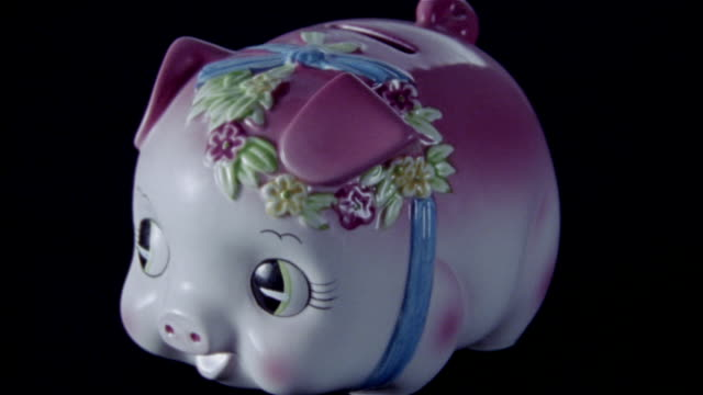 High speed close up piggy bank being smashed with sledgehammer