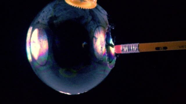 High speed close up tip of pencil eraser bursting bubble on wand