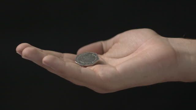 high speed coins falling in to hand, against black - silver metal stock videos and b-roll footage