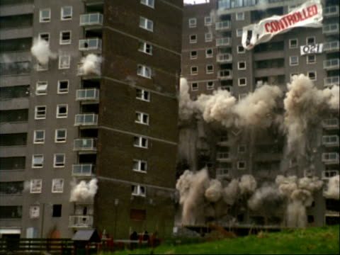 WA high speed demolition of 2 tower blocks, with dust cloud, low angle, Sandwell, Birmingham, UK