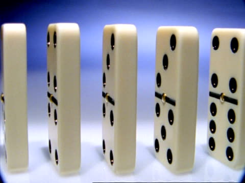High Speed Dominoes - CU row of side angled dominoes evenly spaced falls over across frame
