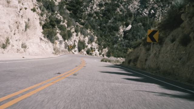high speed pov driving down a winding mountain road - winding road stock videos & royalty-free footage