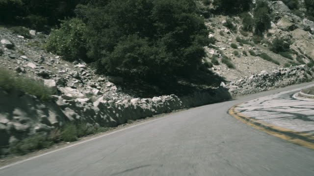 high speed pov driving down a winding mountain road - corner stock videos & royalty-free footage