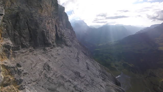 High speed drone flying along cliff with view of alps