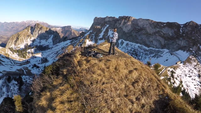 high speed drone flying around pilot on mountain top - piloting stock videos and b-roll footage