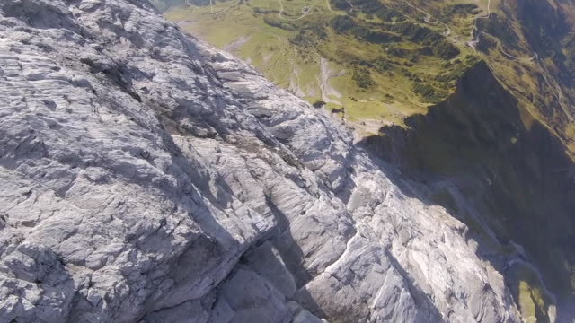 High speed drone flying down cliff and performing acrobatics over ridge