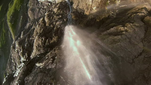 High speed drone flying down cliff and waterfall