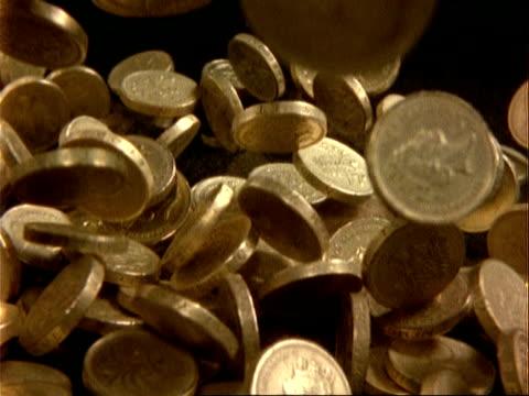 mcu high speed english pound coins fall onto black surface - 年金点の映像素材/bロール