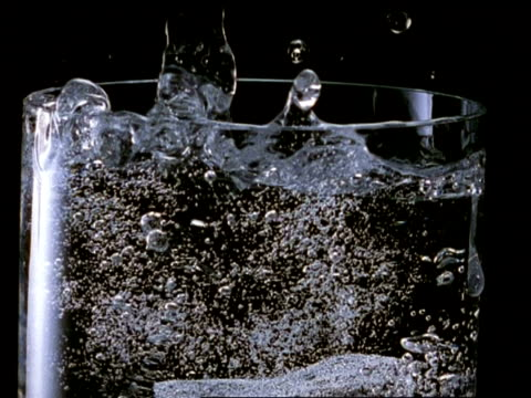 High Speed Ice cube falls into glass of fizzy water, displacing water, black background, most of glass visible