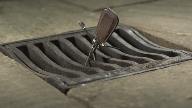 high speed keys falling through drain cover - careless stock videos & royalty-free footage