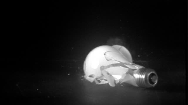 vídeos de stock, filmes e b-roll de high speed light bulb falling and shattering on black surface - lâmpada