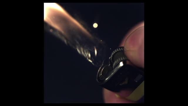 vidéos et rushes de high speed lighter being lit, black background; 2000fps, shutter speed 1/2000 - sparks