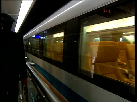 high speed 'maglev' magnetic levitation train pulls into platform at shanghai airport ext back view of train as it pulls away along track int large... - levitation stock videos and b-roll footage