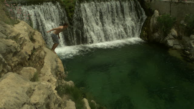 high speed man jumping from rocks into waterfall pool, spain. (individual frames may also be used as a still image. each frame in its raw state is about 6mb or about 12mb as a 16 bit tiff) - campo gravitazionale video stock e b–roll