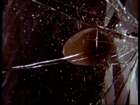 high speed - mcu stone smashing through pane of glass, black background - rompere video stock e b–roll