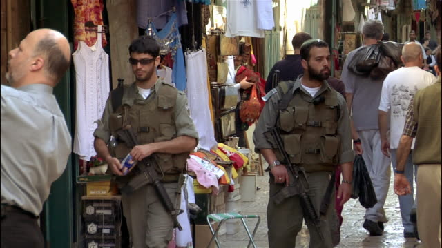 stockvideo's en b-roll-footage met high speed medium shot soldiers patrolling market/ jerusalem - israëlisch leger