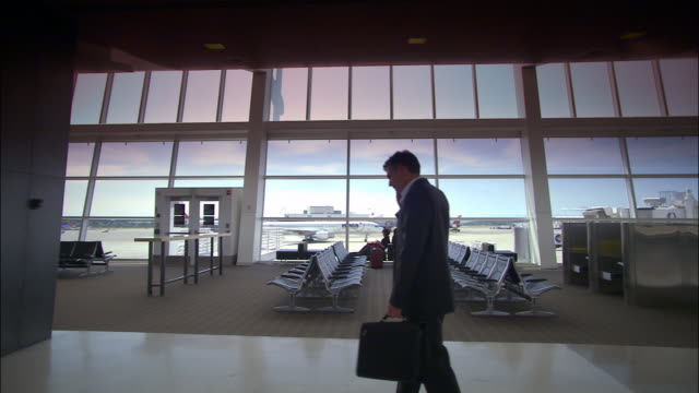 High speed medium shot zoom in businessman at airport gate walking and talking on mobile phone/ Seattle
