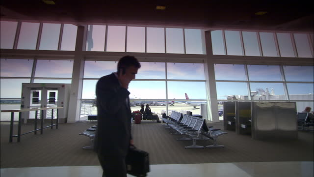 High speed medium shot zoom out businessman at airport gate talking on mobile phone/ Seattle