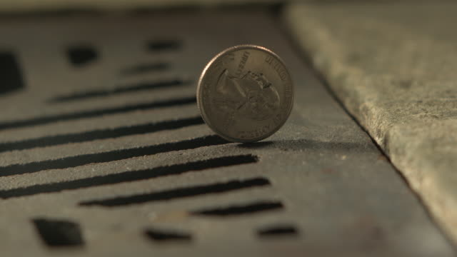 high speed money american quarter dollar spins and falls in to drain - verlust stock-videos und b-roll-filmmaterial