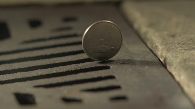 vidéos et rushes de high speed money american quarter dollar spins and falls in to drain - perte