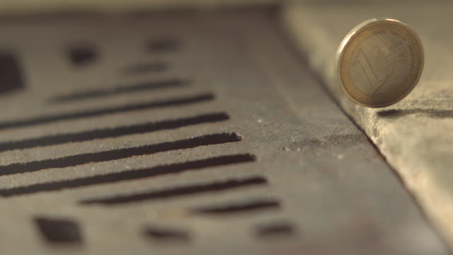 vidéos et rushes de high speed money one euro coin rolls and falls in to drain - coin