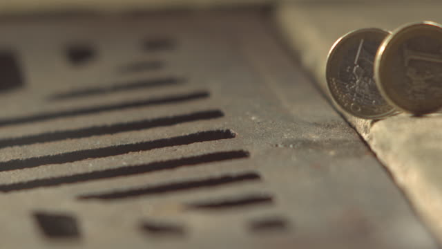 high speed one euro coins roll and fall into drain - loss stock videos and b-roll footage