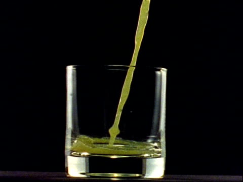 High Speed - CU orange juice pours into glass, black background