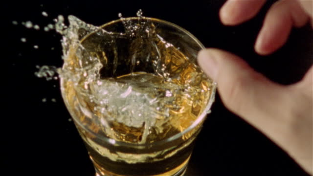 High speed overhead view of ice being dropped into glass of whiskey