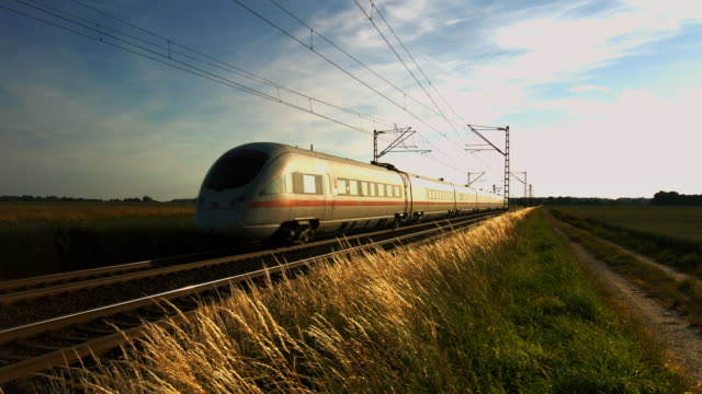 high speed passenger train passing by at sunset - treno video stock e b–roll