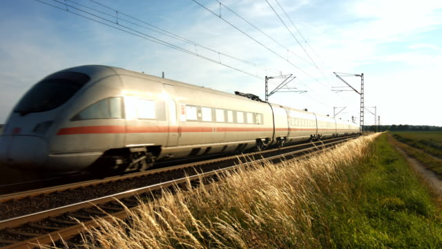high speed passenger train passing by at sunset - schienenverkehr stock-videos und b-roll-filmmaterial