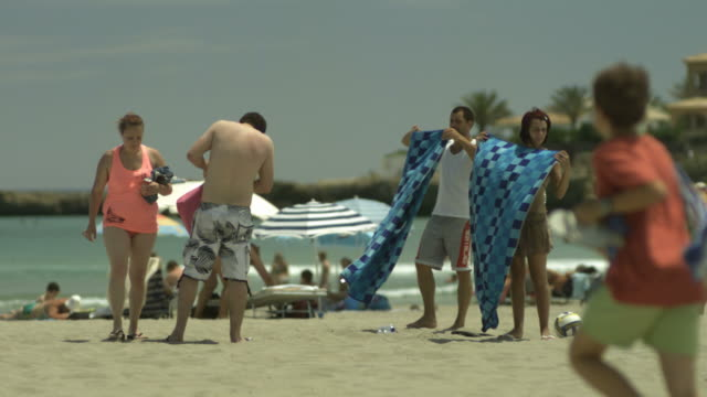 High Speed People shaking out towels on beach, Spain. (Individual frames may also be used as a still image. Each frame in its raw state is about 6MB or about 12MB as a 16 bit TIFF)