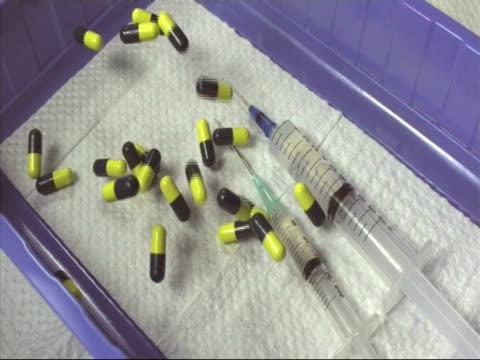 vidéos et rushes de high speed pills and syringe falling into tray - comprimés