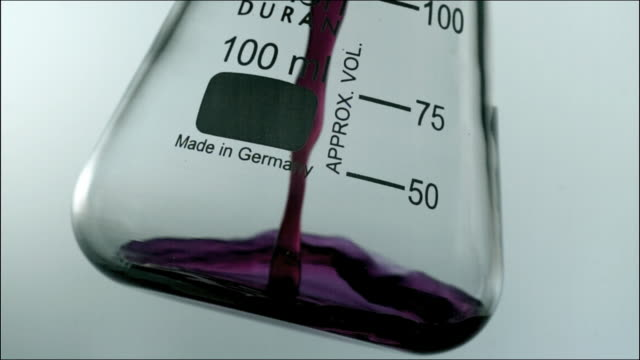 high speed cu purple chemical liquid pouring into glass - volume fluid capacity stock videos & royalty-free footage