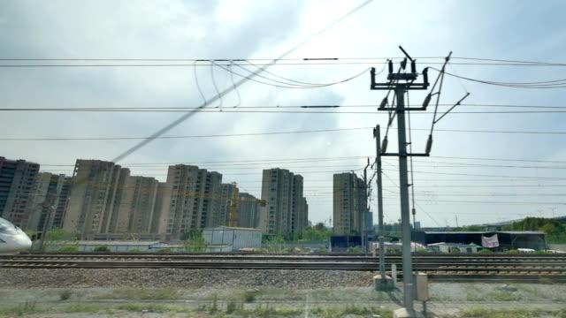 high speed railroad near modern buildings - traliccio elettrico video stock e b–roll