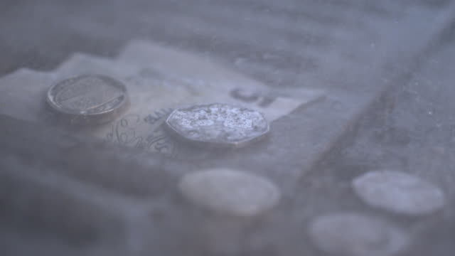 high speed rain falling on uk five pound note and coins in drain - british pound sterling note stock videos & royalty-free footage