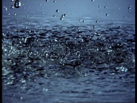 high speed rain falling onto shallow water surface - splashing droplet stock videos & royalty-free footage