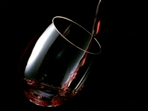 high speed red wine falls into a slanting glass, a black background, filling glass - wine glass stock videos and b-roll footage