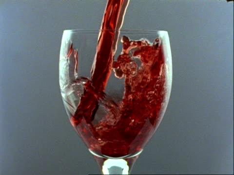 High Speed - CU red wine pours into glass, grey background