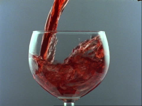 high speed - cu red wine pours into round glass, grey background - drinking glass stock videos & royalty-free footage