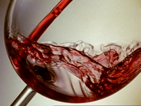 High Speed CU Red Wine pours into the bottom of a slanting glass, a white background, swirling liquid, some spilling