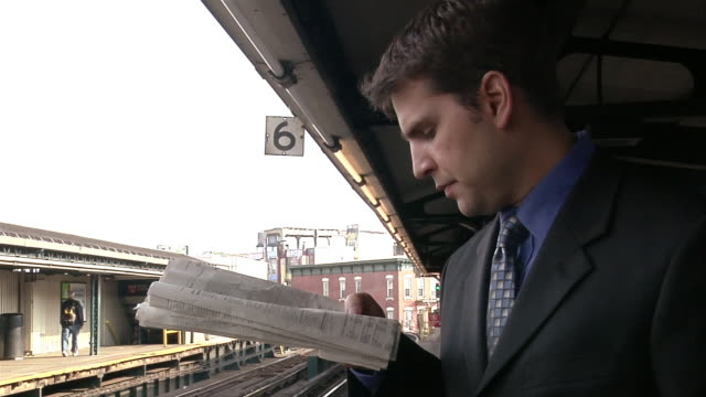 high speed shot of male professional reading newspaper on platform while waiting for train / looking for train - number 6 stock videos & royalty-free footage