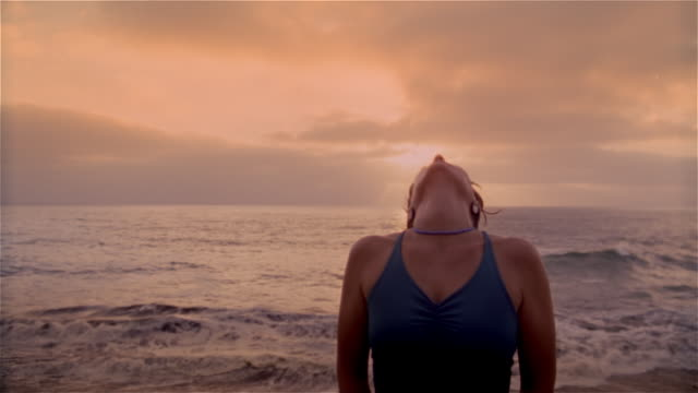 high speed shot of woman tilting head back while doing yoga on beach at dawn / lowering head and looking at camera - head back stock videos & royalty-free footage