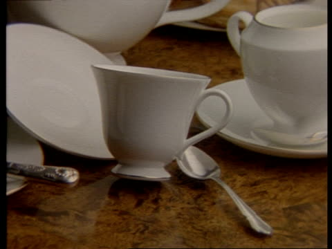 High Speed CU tablecloth pulled from under cup, saucer and milk jug, teacup falls over, spilling tea